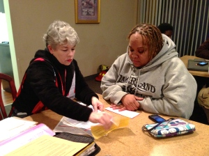 Red Cross volunteer Sheila Miller (l) helps Yvonne Johnson (r) with emergency disaster relief after an early morning blaze burned her home on December 26, 2012. (Photo credit: Anne Florenzano/American Red Cross)
