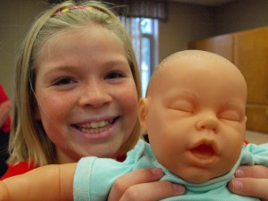 Brianna Kompelien holds up her Red Cross baby. Photo credit: Lynette Nyman/American Red Cross