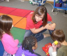 Marie Nordahl, Red Cross Youth Engagement Intern, helps kids practice calling 9-1-1. (Photo credit: Lisa Joyslin/American Red Cross)