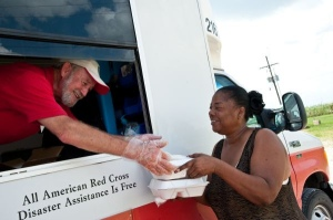 Red Cross volunteer Rick Campion hands food to Janice Lewis during the Hurricane Isaac disaster response, September 1, 2012. (Photo credit: Daniel Cima/American Red Cross)