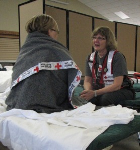 Red Cross disaster relief worker Lori Dehn talks with a shelter resident, Sebeka High School, May 16, 2013.