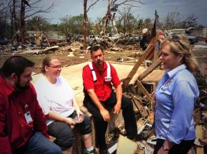 Kimberly Graham lost her home in Moore, Oklahoma. Here, she sits, holding onto a personal picture she found near her home. (Photo courtesy of Red CrossOKC)
