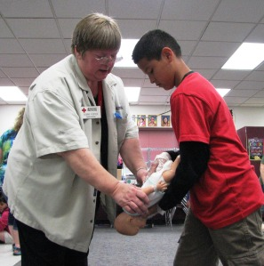 Red Cross instructor Debbie Foster helps a student during a babysitter's training class at Red Lake Elementary school in Red Lake, MN, on June 20, 2013.
