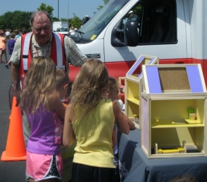 A Red Cross volunteer sparks the conversation about fire safety using a new dollhouse, Maple Grove, Minnesota, 2013.