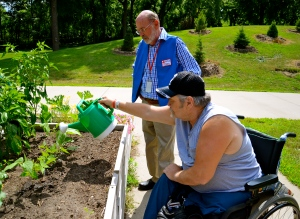 Veteran Bob Hilleshiem and Red Cross worker Mike Booth tend to a garden at the VA Hospital in Minneapolis, July 24, 2013.