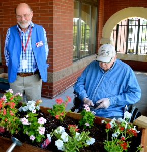 Red Cross worker Mike Booth visits with veteran Harold Palm at the Minnesota Veterans Home garden in Minneapolis, July 24, 2013.