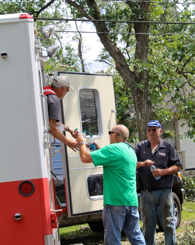 "Red Cross volunteer Rick Campion distributes cold water to local residents Lloyd Baakkonen and Ronald Hines from the ERV.  ""We heard your horn and came running,"" said Baakkonen, who despite having a tree through his roof had a huge smile on his face. ""There's nothing better than cold water."""
