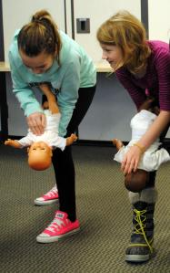 During a Babysitter's Training course in Minneapolis, Minn., youth learn that CPR is performed differently on infants than on children and adults. Techniques are performed here that require hands-on skills focusing on back blows, chest thrusts and proper ways to safely hold an infant. Photo credit: Krista Weiler/American Red Cross