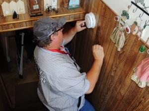 Red Cross volunteer Donny Schreibo installs a smoke alarm in Plainview, MN, on September 19, 2015.