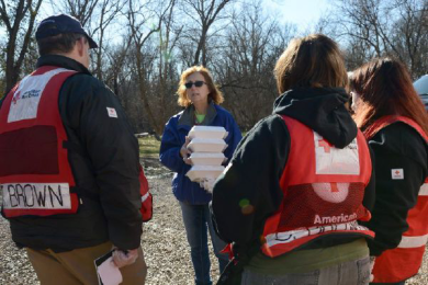 Flood survivor Marcia Walsh welcomes hot meals from Red Cross volunteers James Brown; Sherri Brown and Devyn Brown in Missouri, January 4, 2016. Photo credit: Daniel Cima