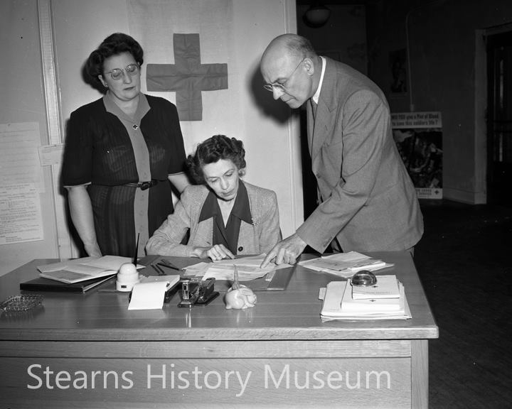 This 1944 Myron Hall photo shows St. Cloud Area Red Cross officials planning for their next project. Anne Kyle is sitting at her desk, John Henry standing on the right and Mrs. J. L. Rivard is off to the left. Photo provided courtesy of the Stearns History Museum
